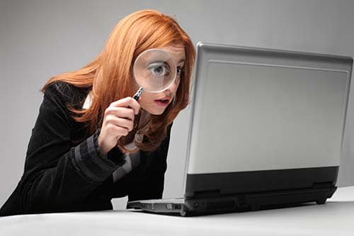 Woman looking at laptop screen with magnifying glass