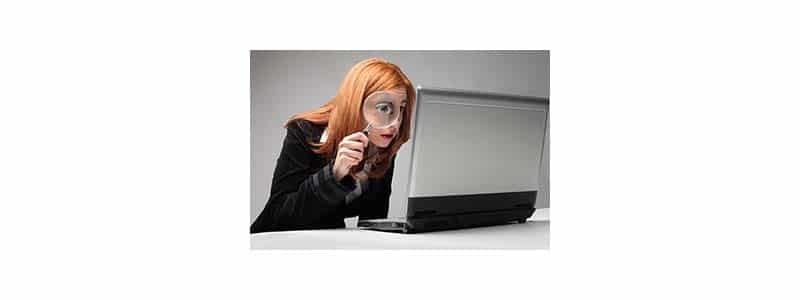 Woman looking at laptop screen through magnifying glass